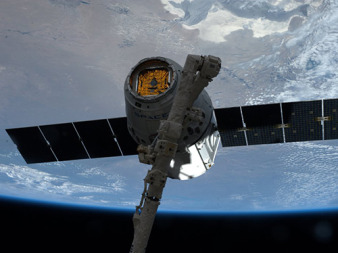 A SpaceX dragon cargo spacecraft is grappled by the station's robotic arm. Credit: NASA