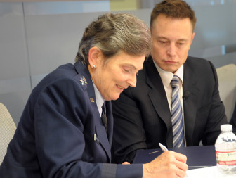 Elon Musk looks on as U.S. Air Force Lt. Gen. Ellen Pawlikowski signs a June 2013 agreement. Credit: U.S. Air Force/ Joe Juarez