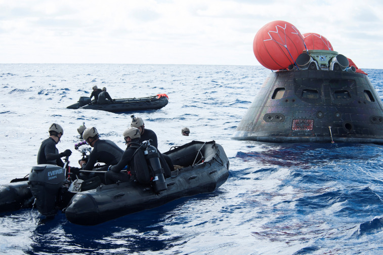 Recovery team members in rigid-hulled inflatable boats approach NASA's Orion spacecraft following its splashdown in the Pacific Ocean. Credit: U.S. Navy