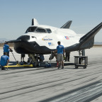 SNC team members check the company's Dream Chaser flight vehicle systems following a 60 mph tow test on taxi and runways at NASA's Dryden Flight Research Center at Edwards Air Force Base in California.  Credit: NASA