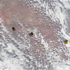 Three cubesats orbit Earth after being deployed from the ISS. Credit: NASA