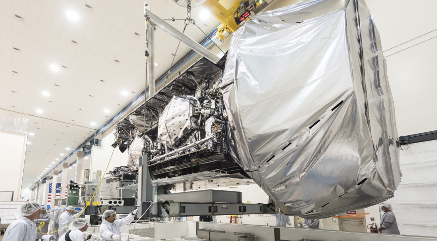 MUOS-4 hangs above its shipping container. Credit: Lockheed Martin