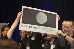 "Moments after the flyby, New Horizons PI Alan Stern held up a now-outdated stamp of Pluto and suggested replacing it with a new one, crossing out the words ""not yet."" Credit: SpaceNews photo by Jonathan Charlton"
