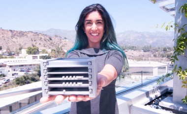 Systems engineer Farah Alibay proudly displays an early 3D-printed model of a  CubeSat radio, developed at the Jet Propulsion Laboratory, capable of transponding with NASA's Deep Space Network. Credit: JPL