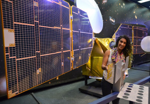 The full-scale mock-up of NASA's MarCO CubeSat held by Farah Alibay, a systems engineer at NASA's Jet Propulsion Laboratory, is dwarfed by the one-half-scale model of NASA's Mars Reconnaissance Orbiter behind her. Credit: NASA/JPL