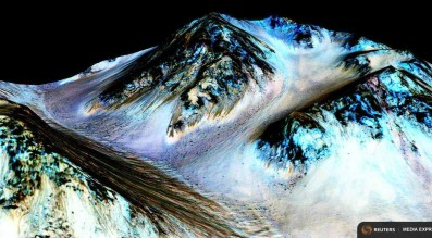 Dark, narrow, 100 meter-long streaks on Mars inferred to have been formed by contemporary flowing water are seen in an image produced by NASA, the Jet Propulsion Laboratory (JPL) and the University of Arizona.  Credit: NASA/JPL/University of Arizona/Handout