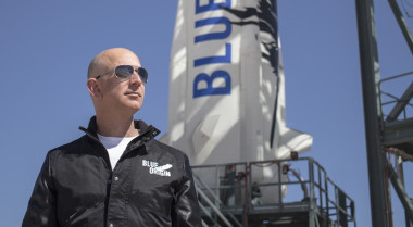 Blue Origin founder Jeff Bezos poses in front of his rocket. Credit: Blue Origin