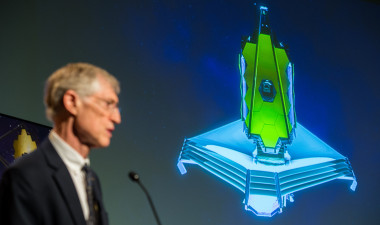JWST Program Scientist John Mather speaking at NASA Headquarters event in 2014 in front of an animation of the 6.5-meter infrared telescope. Photo Credit: NASA/Joel Kowsky