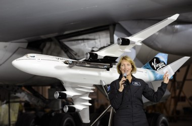 Virgin Galactic test pilot Kelly Latimer stands in front of a model of the 747 that carry LauncherOne, with the actual aircraft in the background, during a Dec. 3 event in San Antonio. Credit: Virgin Galactic