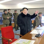North Korean leader Kim Jong Un (C) reacts as he watches a long range rocket launch in North Korea