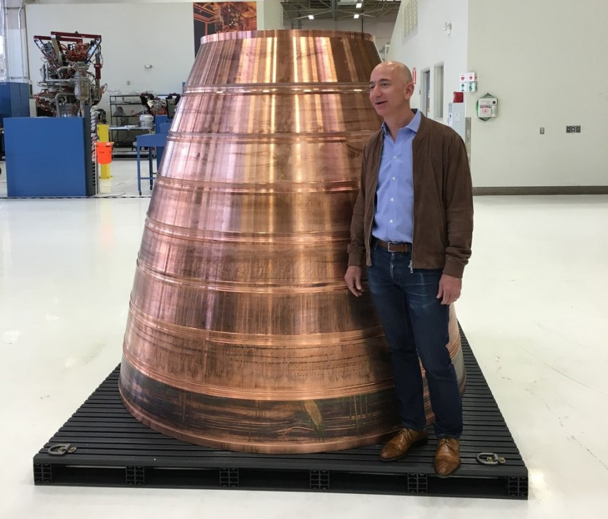 Blue Origin founder Jeff Bezos poses with part of a BE-4 engine nozzle during a media tour of the company's headquarters in Kent, Washington, on March 8. Credit: SpaceNews photo by Jeff Foust