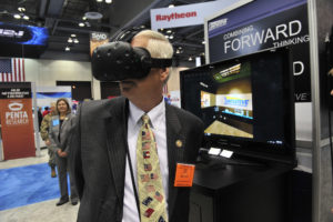 Rep. Mo Brooks (R-Ala.) tries on a virtual reality simulator as he greets vendors and guests at the 2016 Space and Missile Defense Symposium at the Von Braun Center in Huntsville, Ala.  Credit: Eric Schultz / Rocket City Photo