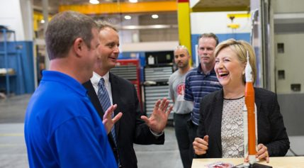Hillary Clinton laughs with Futuramic employees during an Aug. 11 stop at the Warren, Michigan, tool and engineering company. Credit: Michael Davidson for Hillary for America