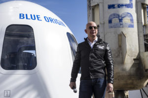 Blue Origin founder Jeff Bezos speaks in front of his company's New Shepard suborbital vehicle on display at the 33rd Space Symposium in Colorado Springs April 5. Bezos said the company still plans to start flying people on suborbital space tourism flights by the end of 2018, although the company has yet to start selling tickets or even setting a ticket price. Development of New Shepard, he said, is informing the company's plans for an orbital launch vehicle, New Glenn, that will use the same BE-4 engines that United Launch Alliance is considering for its Vulcan rocket. Credit: Chuck Bigger for SpaceNews