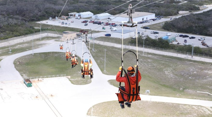 Engineers evaluate the Emergency Egress System as they ride in seats attached to slide wires at Space Launch Complex 41. Credit: NASA/Leif Heimbold