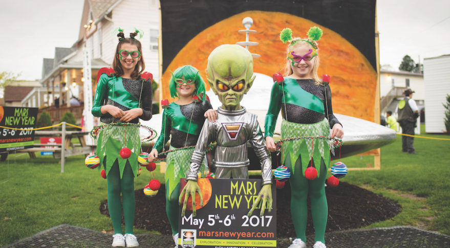 Arabella Wojnar, left, Bianca Wojnar, and Valentina Wojnar, right, pose for a photograph with a model of a spacecraft and alien during the Mars New Year celebration Friday, May 5, 2017, in Mars, Pennsylvania. The town is hosting two days of Science, Technology, Engineering, Arts and Mathematics (STEAM) activities. Photo Credit: NASA/Bill Ingalls
