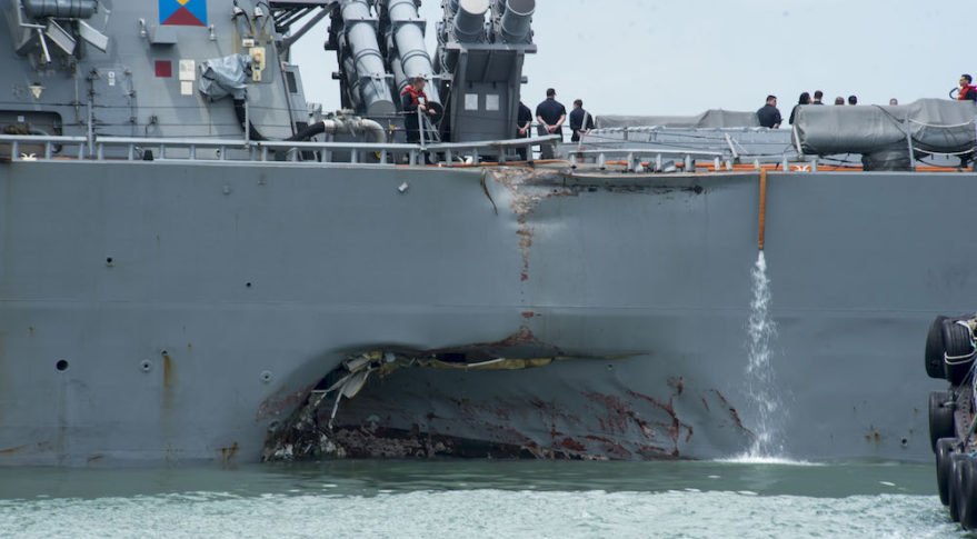 Damage to the portside is visible as the guided-missile destroyer USS John S. McCain steers towards Changi Naval Base in Singapore, following a collision with the merchant vessel. Credit: U.S. Navy
