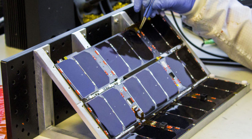A technician works on a double deployed cubesat in the Clyde Space clean room. Credit: Clyde Space
