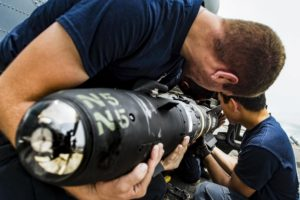 Weapon technicians load an AGM-114 Hellfire missile. (Navy photo)