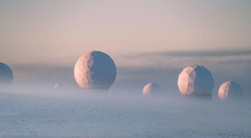 SG-22, the alternate JPSS antenna, sits in icy fog amongst other KSAT radomes in Svalbard, Norway. Credit:  Reuben Wu/Raytheon