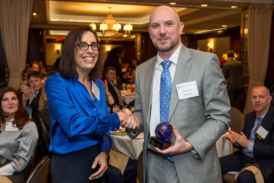Planet's Rich Leshner accepts the Breakthrough of the Year Award from SpaceNews correspondent Debra Werner. Credit: Kate Patterson for SpaceNews.