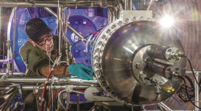 A NASA technician works on a 10-kilowatt Stirling Power Conversion Unit at Glenn Research Center. (Credit: NASA Glenn Research Center)