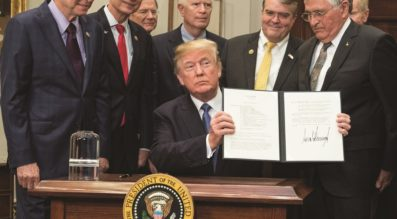 President Trump holds up his freshly signed Space Policy Directive 1 during a Dec. 11 ceremony at the White House. (Credit: White House)