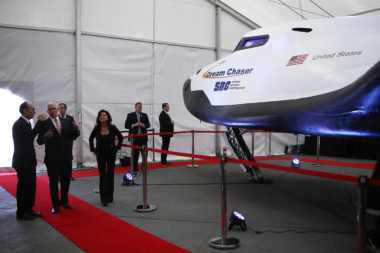 U.S. Vice President Mike Pence, second from left, tours SNC's Dream Chaser exhibit in April 2018 at the 34th Space Symposium  with SNC owners Fatih and Eren Ozmen. Credit: Tom Kimmell for SpaceNews