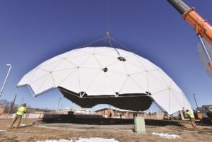 Construction workers at Offutt Air Force Base, Nebraska, move a protective enclosure in February as part of transition to new terminals that work with Wideband Global SATCOM satellites. Credit: U.S. Defense Department