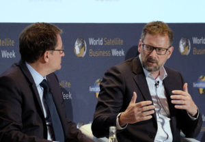 Steve Collar, SES president and chief executive, is shown talking to  Rodolphe Belmer, Eutelsat chief executive, during a satellite operators panel at the World Satellite Business Week conference in Paris in September 2018. Credit: SpaceNews/Brian Berger