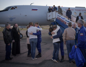 Russian cosmonaut Alexey Ovchinin and U.S. astronaut Nick Hague embrace their families after landing at the Krayniy Airport in Baikonur, Kazakhstan. Their Soyuz MS-10 capsule landed  east of the Kazakh town of Dzhezkazgan after their mission was aborted by a launch failure. Photo Credit: NASA/Bill Ingalls