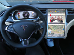 2012 Tesla Model S digital screens. The central bottom touchscreen shows a google map view with live traffic updates, and the top screen shows teslamotors.com site.  Credit: Steve Jurvetson