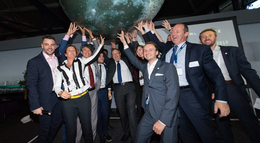 ESA Director General Jan Woerner (center) and Nicolas Chamussy, executive vice president of space systems at Airbus Defence and Space (second from right) get some help from organizers of The Moon Race holding up the inflatable moon that made the rounds at the 2018  International Astronautical Congress in Bremen, Germany, Oct. 1-5. Credit: ESA photo by Philippe Sebirot