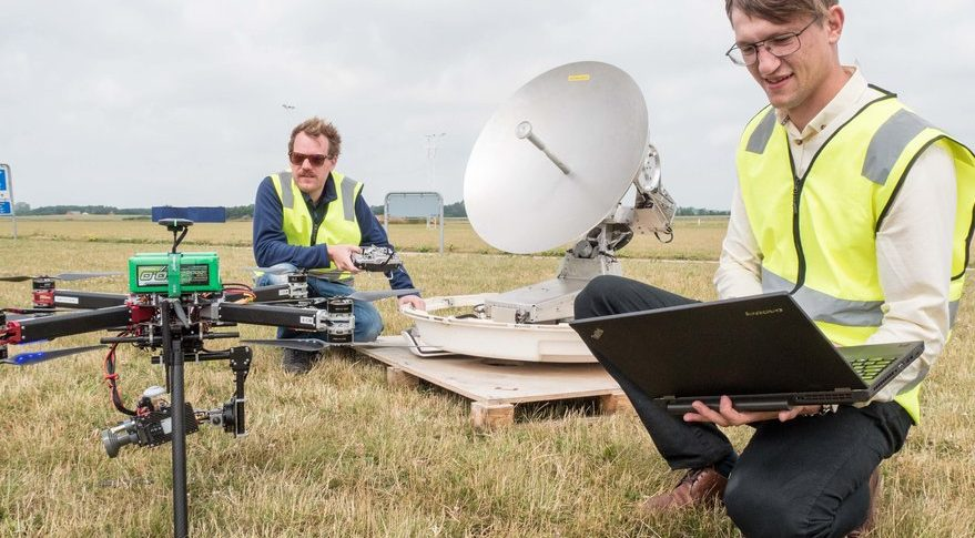 In the foreground, Andrian Buchi, QuadSat co-founder and chief technology officer, programs the QuadSAT drone for satellite antenna testing. Credit: QuadSat
