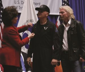 "U.S. Transportation Secretary Elaine Chao pins FAA astronaut wings on SS2 pilot Frederick ""CJ"" Sturckow during a Feb. 7 ceremony in Washington as Virgin Galactic founder Richard Branson looks on. Credit: FAA Office of Communications"