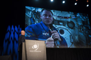 Gen. Jay Raymond, commander of Air Force Space Command, surprises an audience at the 35th Space Symposium with a live video feed from the International Space Station featuring Air Force Col. Nick Hague, NASA Astronaut, in Colorado Springs, Colo., April 9, 2019. Credit: U.S. Air Force