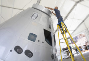 Elias Rodriguez puts the finishing touches on the Lockheed Martin full-scale mockup of its Orion space capsule April 8 before its unveiling at the 35th Space Symposium at the Broadmoor Hotel in Colorado Springs, Colorado. (Keith Johnson/SpaceNews)